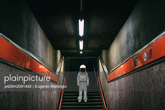 Astronaut on stairway in train platform - p429m2091442 by Eugenio Marongiu