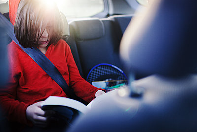 Boy reading book while traveling in car - p1166m1474254 by Cavan Images