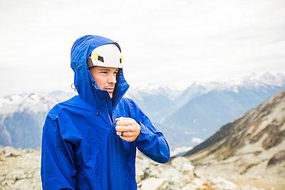 Portrait of mountain climber zipping up rain jacket. - p1166m2162489 by Cavan Images