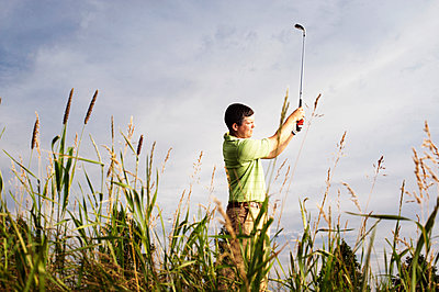 Side view of male golfer swinging golf club on field against sky - p1166m969518f by Cavan Images