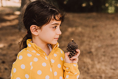 Cute girl holding pine cone while looking away in park - p300m2225751 by Eloisa Ramos