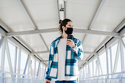 Young man wearing face mask looking away while using mobile phone standing on bridge - p300m2242376 by Eva Blanco