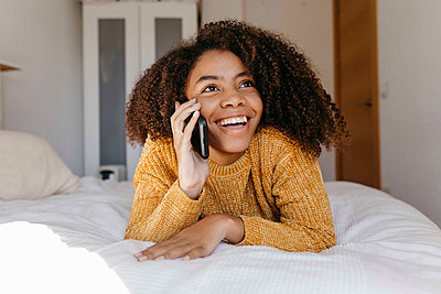 Smiling woman talking on mobile phone while resting at home - p300m2256657 by Tania Cervián