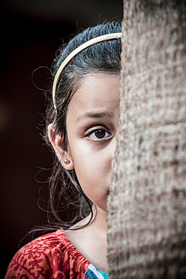 Scared little girl hiding behind tree - p794m966723 by Mohamad Itani