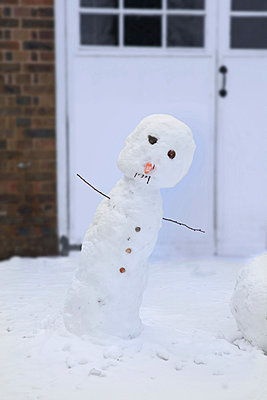 Leaning snowman in front of garage - p924m806962f by Simon Battensby