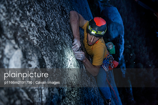 Top view man rock climbing at night above the sea and highway - p1166m2191790 by Cavan Images