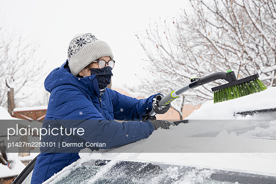 USA, New Mexico, Santa Fe, Woman in face mask removing snow from car - p1427m2283101 by Dermot Conlan