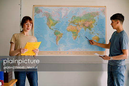 Teenage girl reading while boy pointing on world map in classroom - p426m2298645 by Maskot