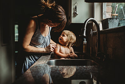 Mother bathing shirtless daughter in kitchen sink at home - p1166m1543898 by Cavan Images