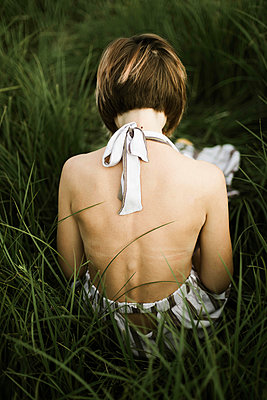 Back view of the woman in dress sitting on grass - p1166m2094571 by Cavan Images