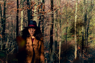 Sad woman looking down while standing in forest - p300m2240479 by Francesco Morandini