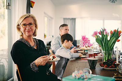 Portrait of smiling grandmother having cake while sitting with family at table during party - p426m1580206 by Maskot