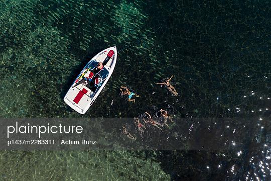 Junge Leute schwimmen neben einem Motorboot - p1437m2283311 von Achim Bunz