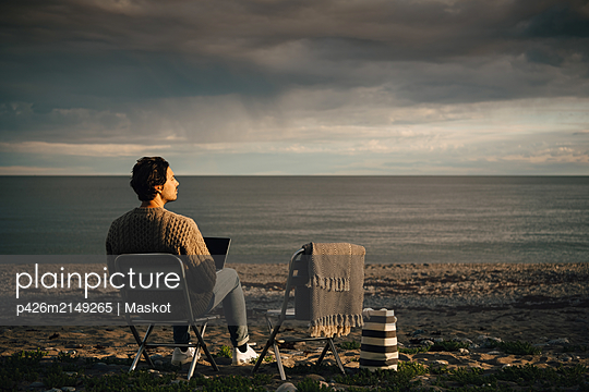 Thoughtful man using laptop while sitting at beach against cloudy sky - p426m2149265 by Maskot