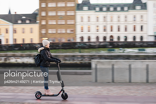 Side view of teenage girl riding electric push scooter on street in city - p426m2149271 by Kentaroo Tryman