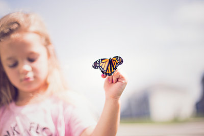 Butterfly taking flight from young conservationist. - p1166m2096364 by Cavan Images