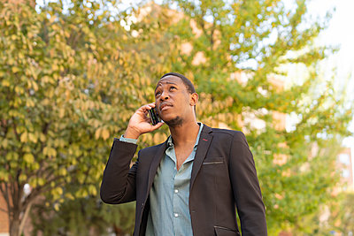 young stylish african man in the city talking from mobile phone - p1166m2218271 by Cavan Images