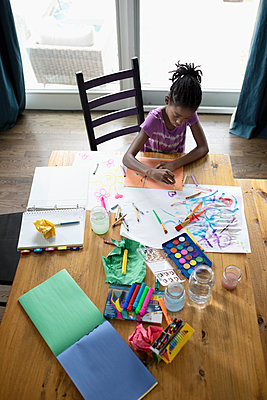 Girl coloring and painting at dining table - p1192m2046977 by Hero Images