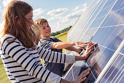 Boy and girl touching solar panels - p312m1533421 by Hans Berggren