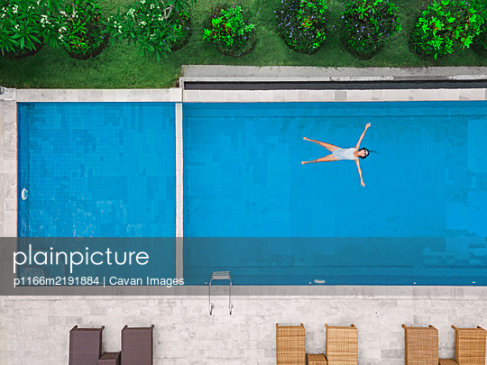 Aerial view of attractive woman floating over water at resort - p1166m2191884 by Cavan Images
