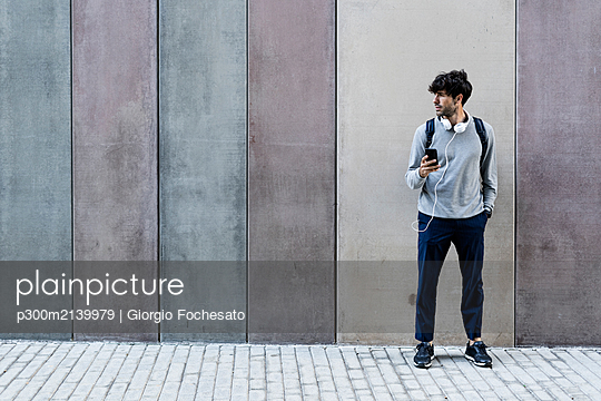 Man with cell phone and headphones standing in front of awall - p300m2139979 von Giorgio Fochesato