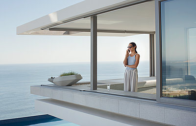 Woman talking on cell phone on modern, luxury home showcase exterior patio with ocean view - p1023m1530937 by Tom Merton