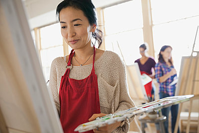 Woman painting in art class - p1192m1031691f by Hero Images