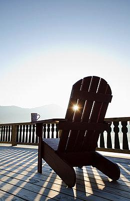 USA, New York, Lake Placid, Adirondack chair on deck by lake - p1427m2254871 by Chris Hackett