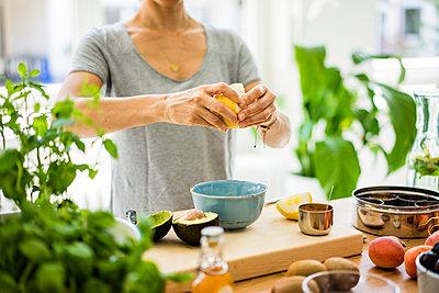Woman preparing healthy food in her kitchen - p300m2069251 von Robijn Page