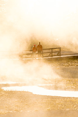 Mother and daughter looking at geyser, West Thumb Geyser Basin, Yellowstone National Park, Wyoming, USA - p343m2047064 by Kennan Harvey