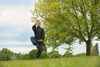 Mature man performing Tai Chi in countryside - p429m802995f by Colin Hawkins
