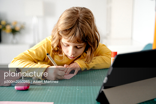 Cute girl drawing on paper with digital tablet on desk at home - p300m2250285 by Albert Martínez