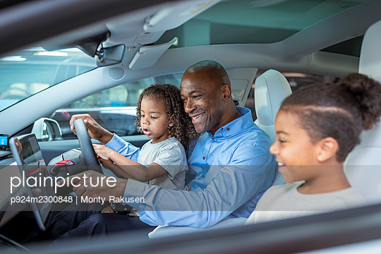 UK, Father with daughter (2-3) and son (8-9) sitting in car - p924m2300848 by Monty Rakusen