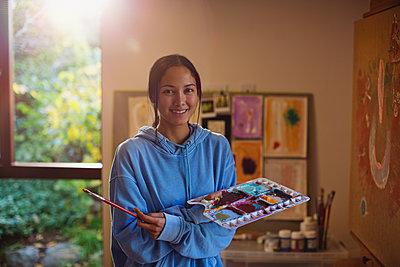 Portrait smiling female artist painting in art studio - p1023m2073939 by Tom Merton