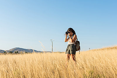 Young woman is taking a picture with a camera in a meadow at sun - p1166m2129524 by Cavan Images