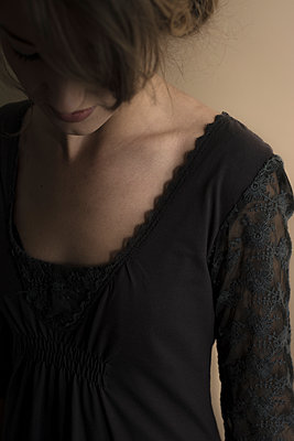 Dark, soft image of young woman looking down. - p1433m1574951 by Wolf Kettler