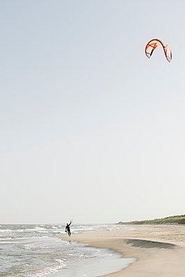 Kiteboarder prepairing his kite at the beach - p300m2118684 by Hernandez and Sorokina
