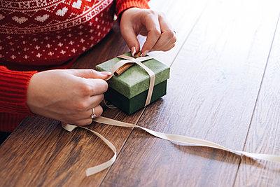Woman's hands decorating Christmas present - p300m2144175 von Mosuno Media
