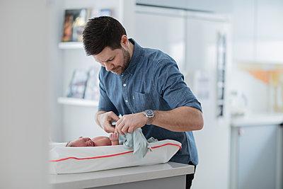 Man changing babys diaper - p312m2077857 by Jonas  Gunnarsson