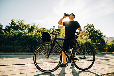 Sportsman drinking water while standing on footpath against sky on sunny day - p426m2270826 by Maskot