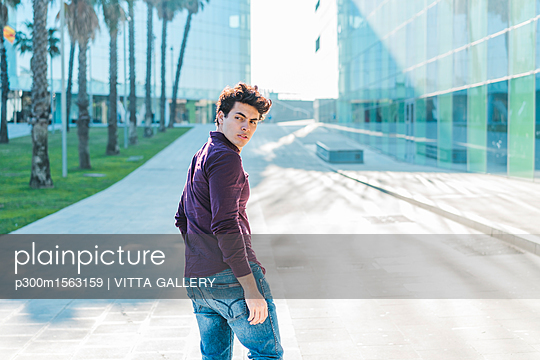 Serious young man walking in the city turning round - p300m1563159 by VITTA GALLERY