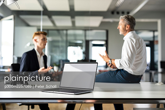 Laptop on table with business people having discussion in background at open plan office - p300m2257089 by Peter Scholl