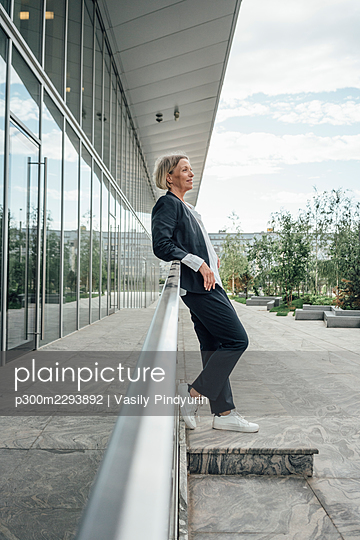 Mature businesswoman looking away while leaning on railing - p300m2293892 by Vasily Pindyurin