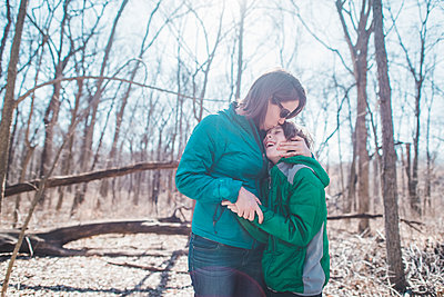 Mother embracing son while standing in forest - p1166m1489893 by Cavan Images