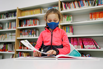 Little girl wearing a medical mask and reading a book in a libra - p1166m2232519 by Cavan Images
