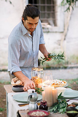Man preparing a romantic candelight meal outdoors - p300m2068804 by Alberto Bogo