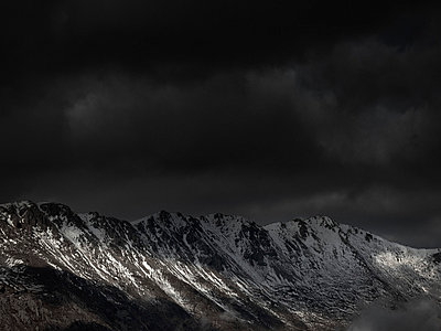 An ominous sky with some sunlight breaking through over a mountain range - p301m844083f by Pep Karsten