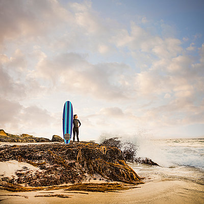 Caucasian surfer with board on beach - p555m1419625 by Mike Kemp
