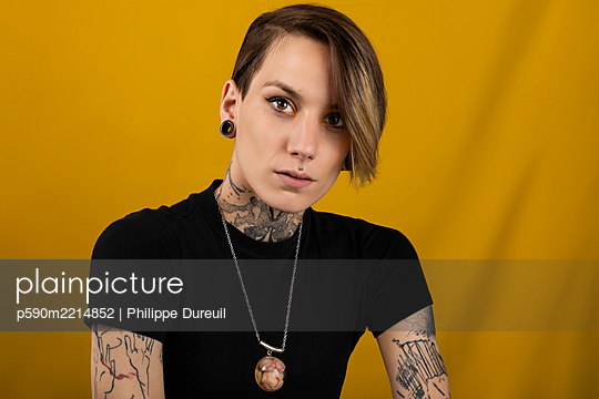 Portrait of a young tattooed woman with piercing and plug - p590m2214852 by Philippe Dureuil