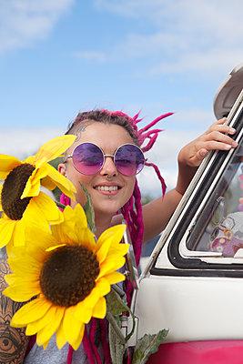 Frau steht vorm VW-Bus mit Sonnenblumen - p045m1591566 von Jasmin Sander